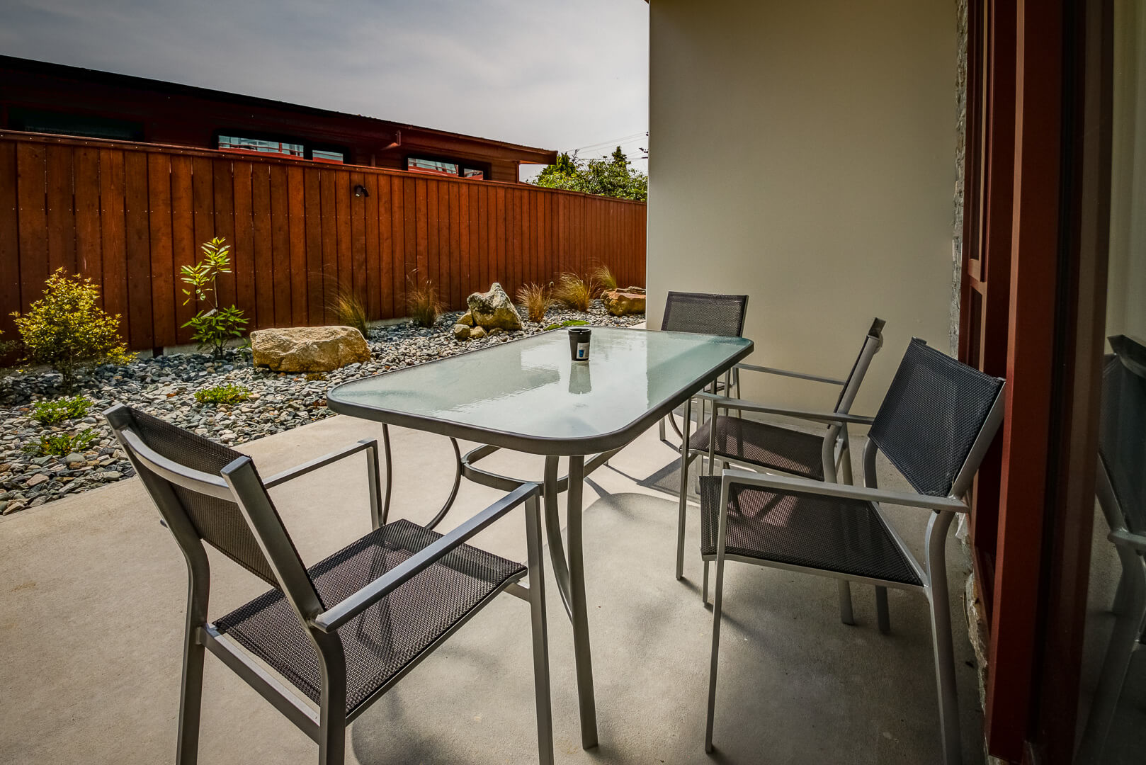 Outdoor table and chairs on the patio of Red Tussock Motel's ground floor unit.