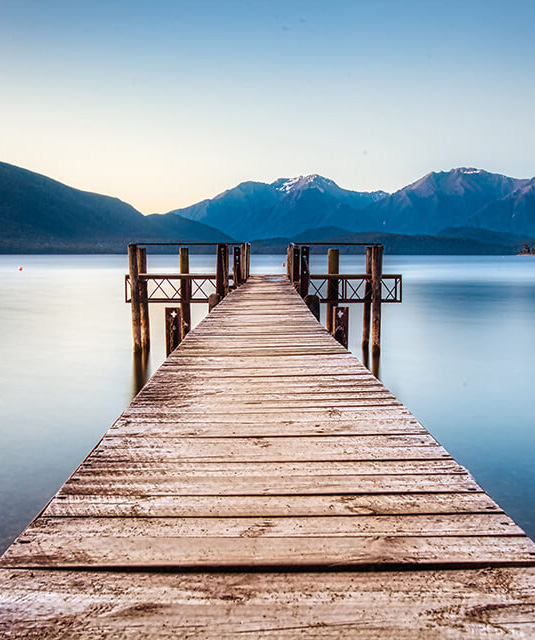 Looking along the length of the Marakura Yacht Club wharf out onto the waters of Lake Te Anau and Mount Luxmore.