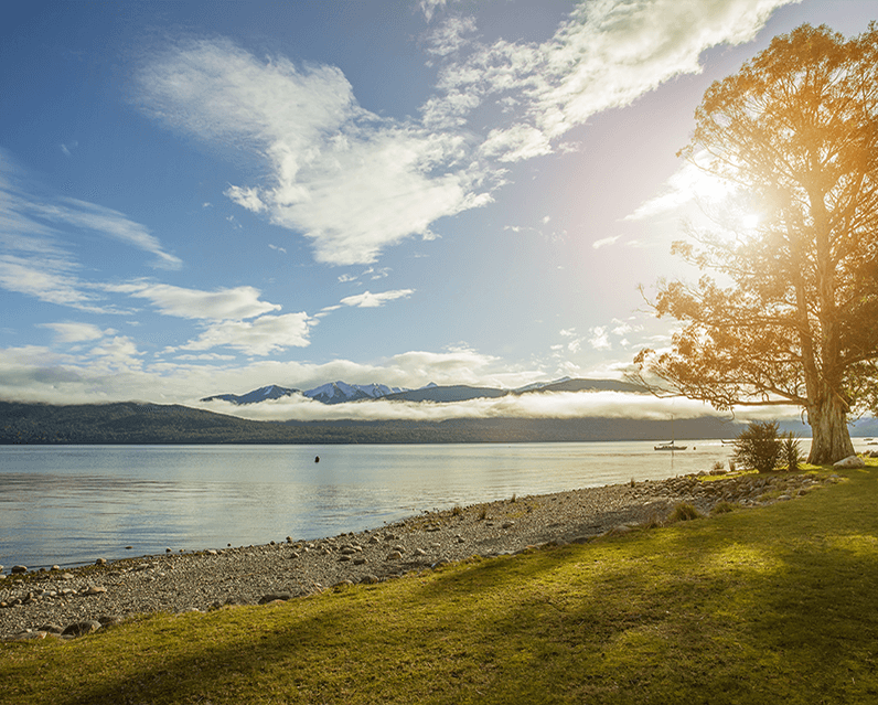 View from the shores of Lake Te Anau towards the water and Mount Luxmore.