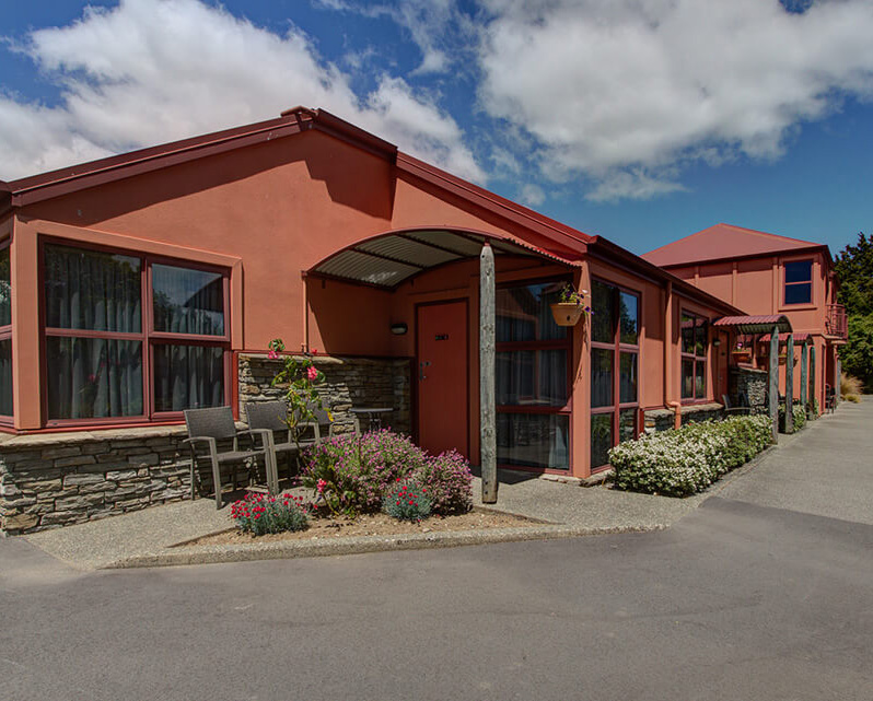 Single storey dusky pink coloured buildings that are the rear of the Red Tussock Motel units