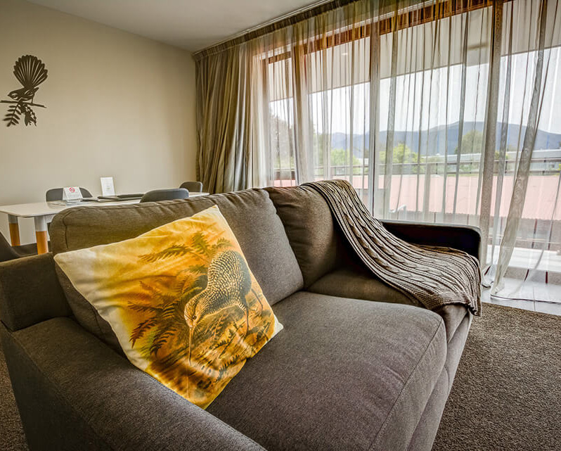 Indoor scene of a Red Tussock Motel unit with a kiwi cushion atop a modern grey coloured couch.