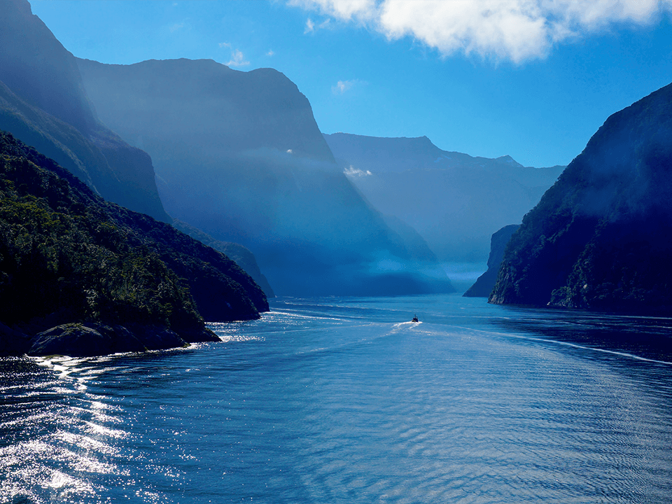 View along Milford Sound with a small boat in the distance.