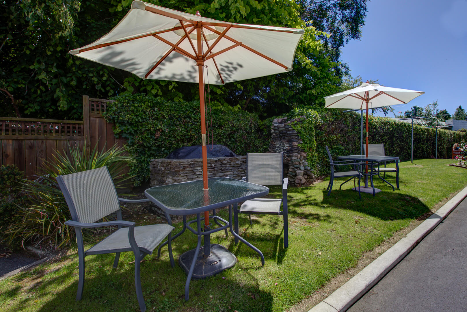 Red Tussock Motel's outdoor grassy area with tables, chairs and umbrellas set up.