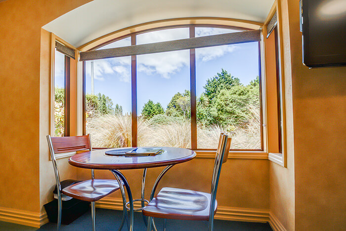 Red Tussock Motel's Superior Queen Studio dining area with table and two chairs looking out window to the tussocks
